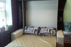 Шкаф-кровать с диваном и подлокотниками.